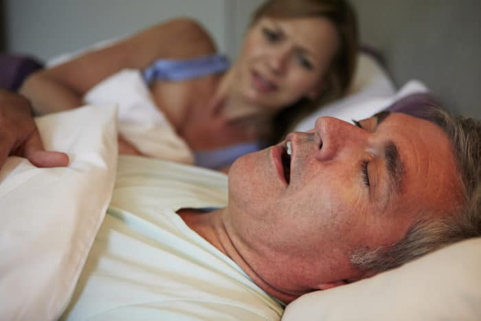 Woman awake in bed due to snoring husband may want to know what is sleep apnea