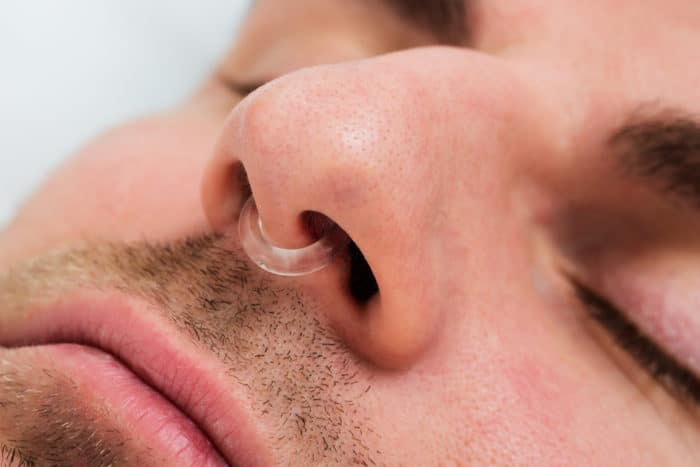 Man with anti-snoring device in nose