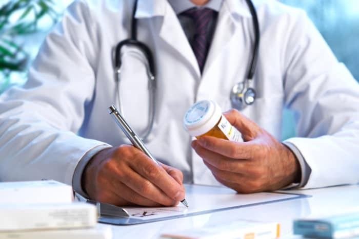 doctor writing a drug prescription for insomnia treatment