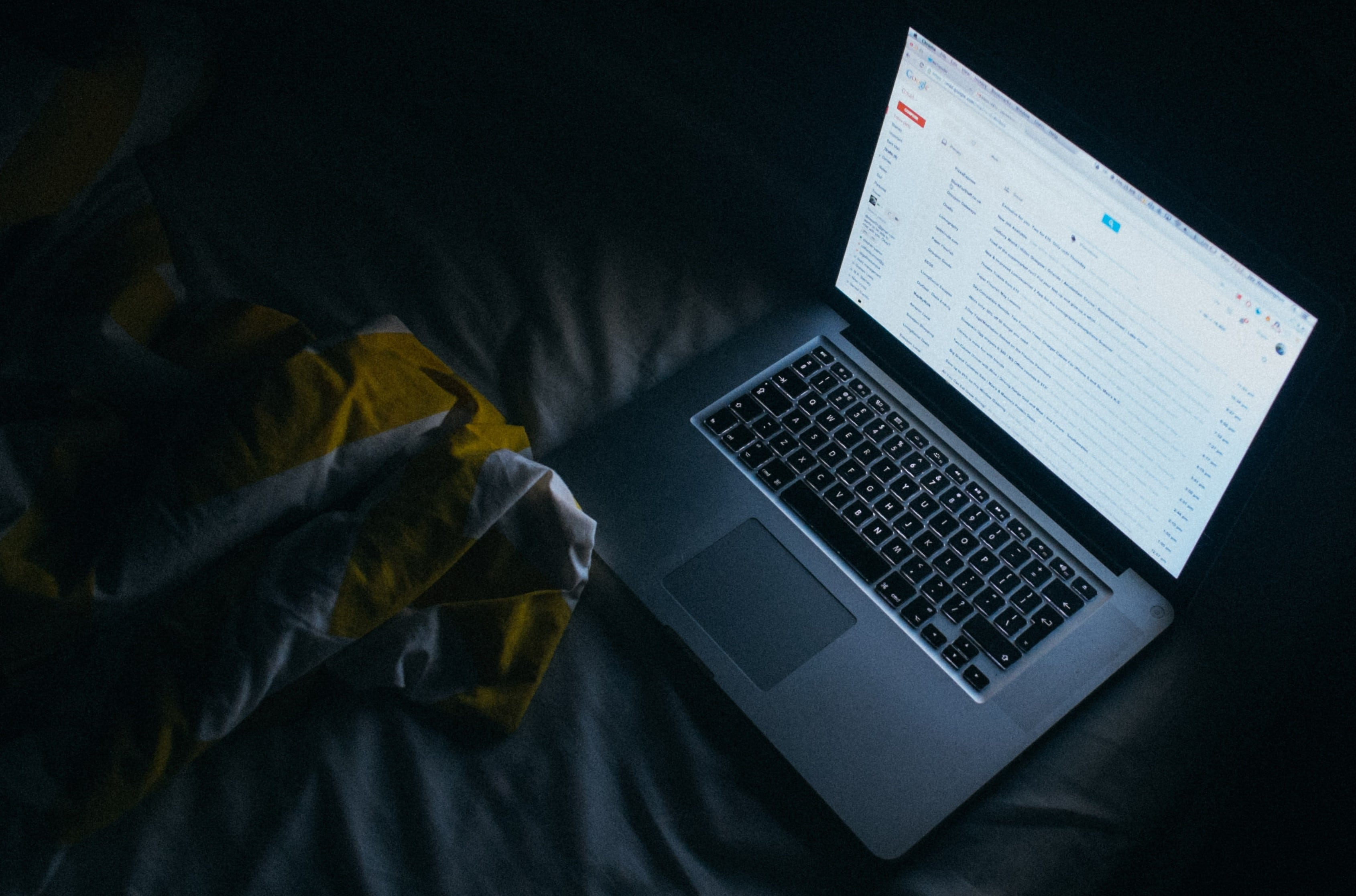 laptop on a bed in the evening emitting harmful bright light that blue light blocking glasses can be used for protection
