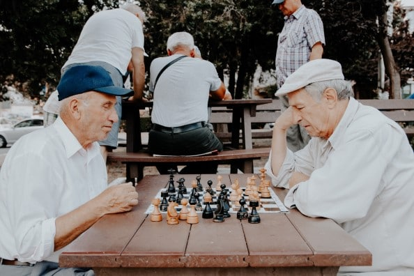 two older men playing chest in the park at a picnic table which may help reduce their risk for dementia