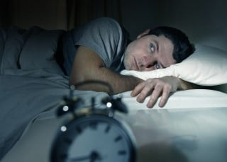 man wide awake at night wondering about insomnia and sleep