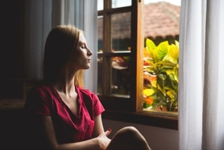 picture of lady meditating by the window for pain management