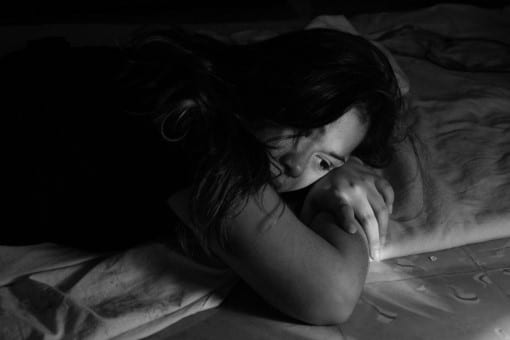 woman with chronic pain awake in bed wondering how to go to sleep