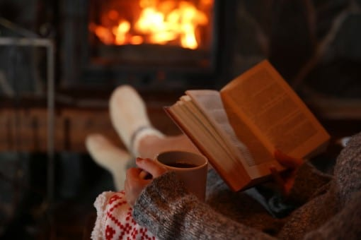 Person relaxing before bed with a cup of tea by the fireplace as described on the sleep checklist