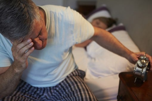 man at risk for diabetes wide awake in bed fighting insomnia
