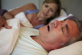 Snoring man with sleep apnea asleep in bed on his back