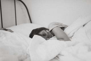 teen in bed may wonder if sleeping too much can cause acne