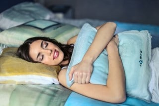 picture of lady resting peacefully in bed so sleep can help her nausea
