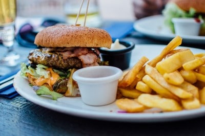 Picture of hamburger and fries which is a food that can sleep apnea and pain worse