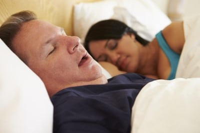 Man snoring at night which will cause a sore throat