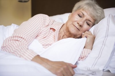 lady sleeping on her side to prevent snoring and sore throats