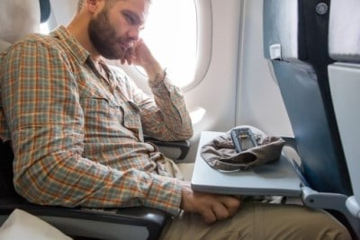 Man sitting on plane who can't sleep during holidays because of jetlag