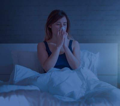 lady in bed wondering whether snoring is causing her nose bleeds