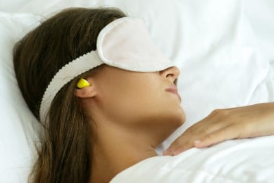 women using ear plugs to help her sleep better