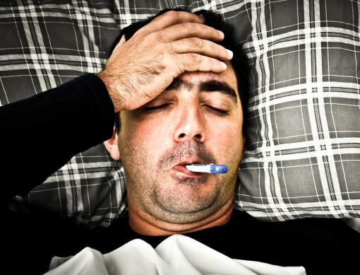sick man awake in bed with thermometer in mouth
