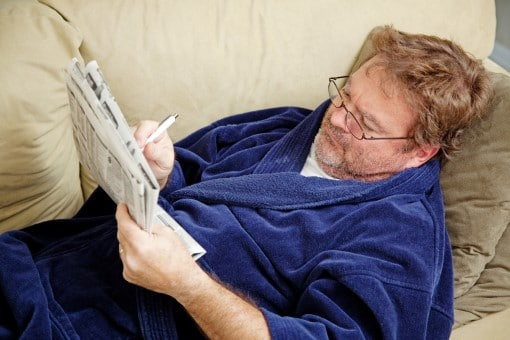 Man worried about coronavirus and a recession checking news paper instead of sleep