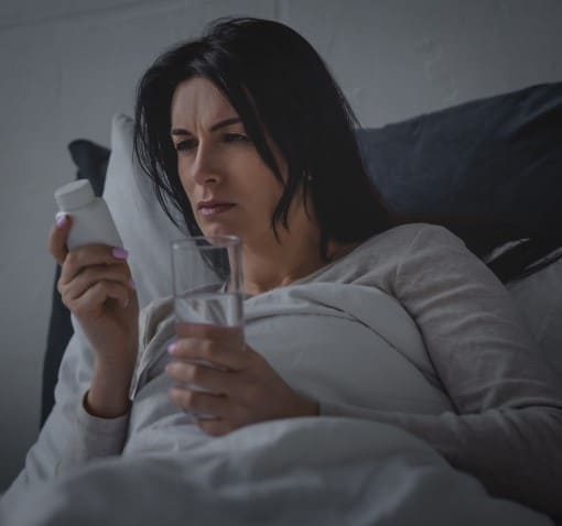 Women awake in bed worried her pain meds are keeping her awake