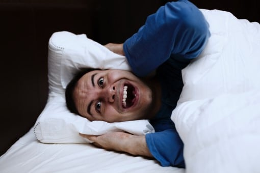 frustrated man awake in bed who wants the best fan for white noise
