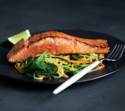 plate salad and salmon showing a healthier meal that can help you treat sleep apnea yourself