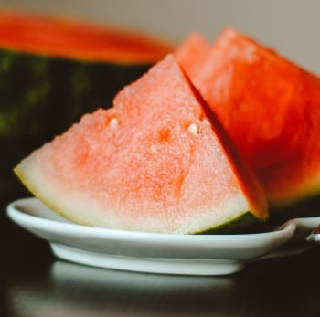 watermelon slices on table which is to be avoided when too hungry to sleep