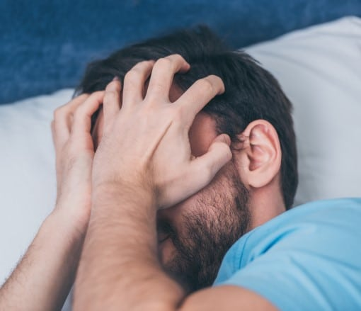 man frustrated in bed showing how people feel when CPAP stressing you out
