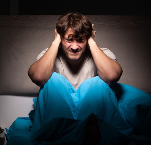 photo of frustrated man awaken during night by noise from smart phone