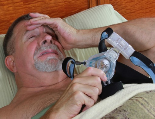 photo of man in bed holding his mask and having a cpap panic attack
