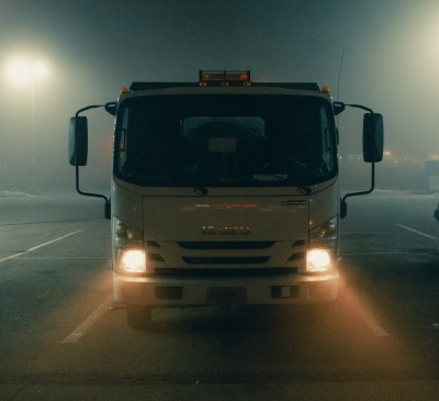 photo of truck at night who's driver may be falling asleep while working