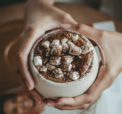 photo of holding cup to drink their hot chocolate before bed with marshmallows