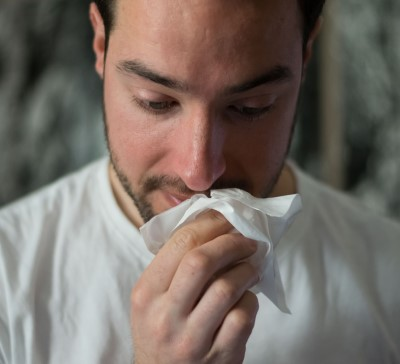 photo of man with runny nose from sleeping with a dog with allergies